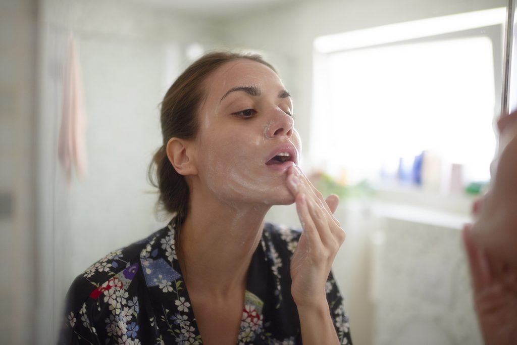 woman applying skincare products to her face