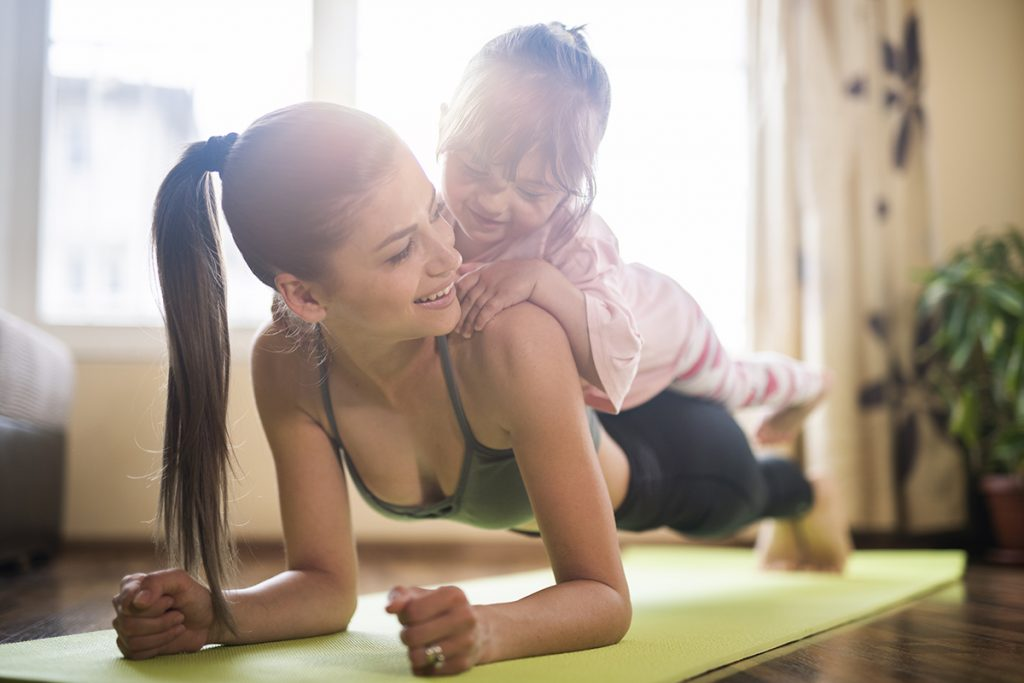 Woman doing yoga with daughter on back