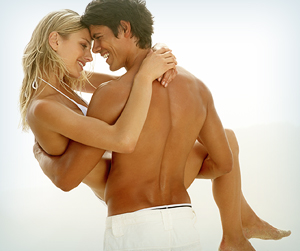 Tan, attractive shirtless male holding a woman in a bikini