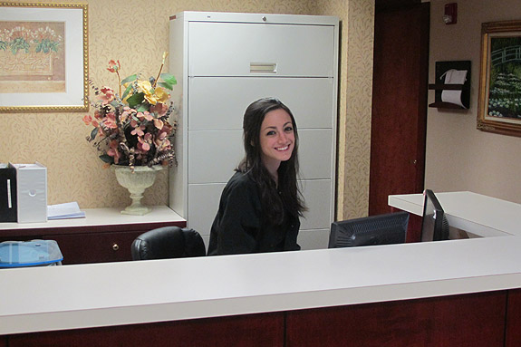Friendly looking young woman behind the reception desk