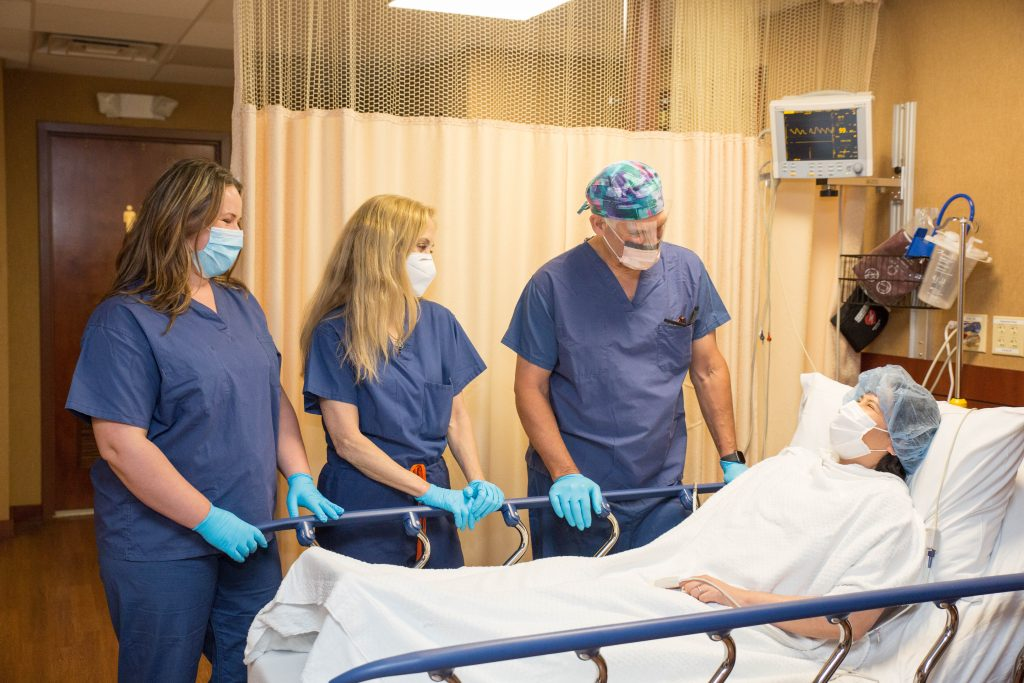 Dr. Parker and 2 staff in scrubs talking with patient who is ready for the operating room