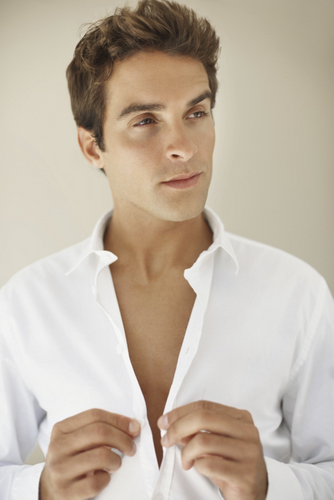 Handsome young man buttoning shirt looking away