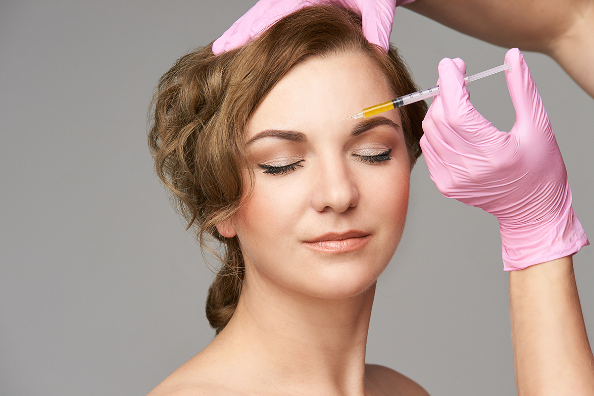 Woman receiving Jeuveau injection in her brow